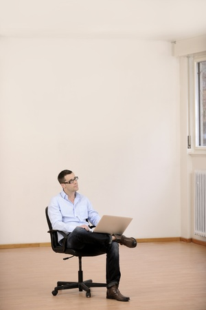 Businessman with laptop in new office  with copyspace photo