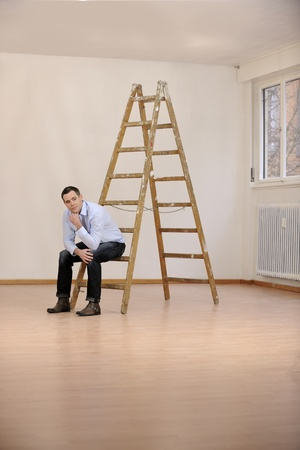 Moving to new office or house: man sitting on ladder in empty room photo