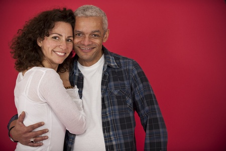mid adult couple: portrait of a mid adult couple hugging on red background Stock Photo
