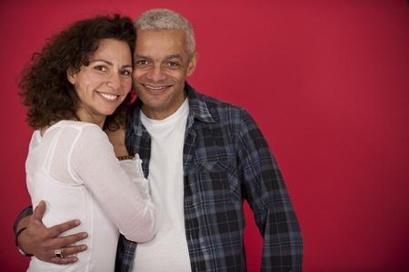 mid adult couple: retrato de una pareja de adultos a mediados abrazando sobre fondo rojo