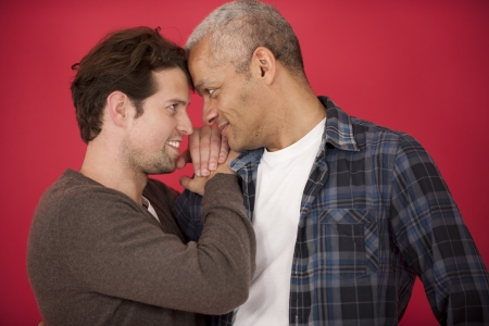 gay men: Happy gay couple in love on red background