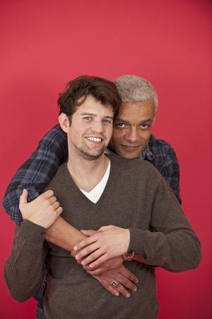 amor gay: Feliz pareja de homosexuales en el amor sobre fondo rojo Foto de archivo