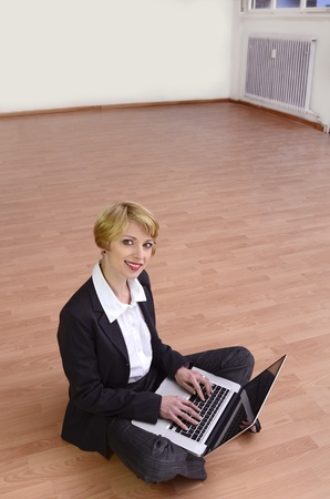 Moving to new office: Businesswoman with laptop in empty room photo