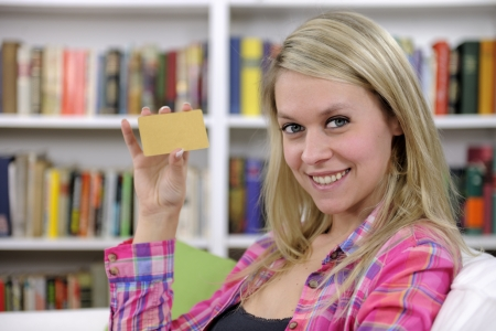 young woman with credit card smiling at home photo