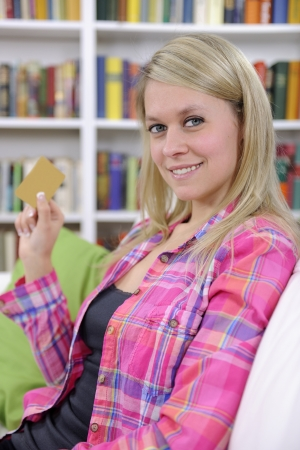 young woman with credit card smiling at home Stock Photo - 13892072