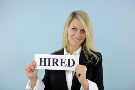 hired: happy young busineswoman holding hired sign Stock Photo