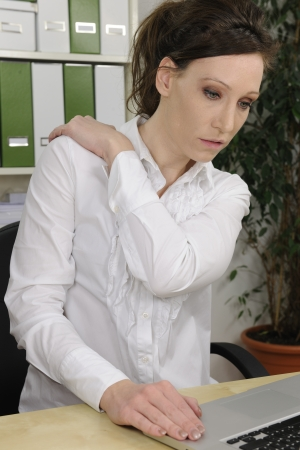 Portrait of young business woman suffering from severe neck pain photo