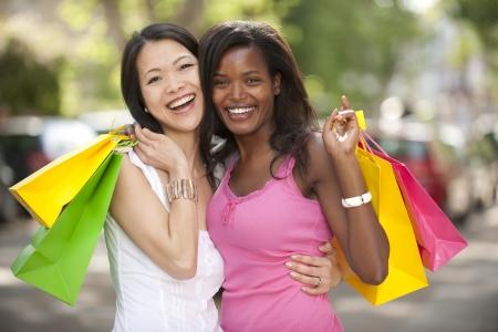 mejores amigas: amigos felices multi�tnicos con bolsas de la compra Foto de archivo