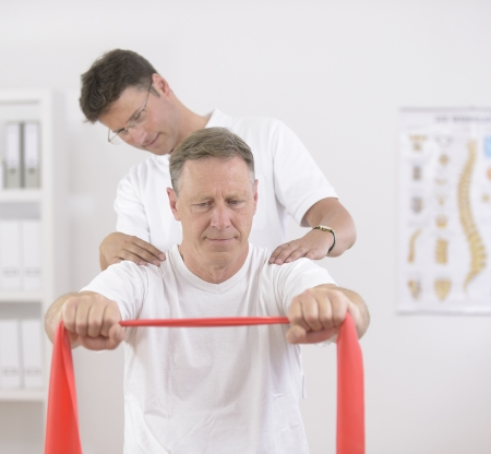strength therapy: Physiotherapy  Senior man doing exercise under supervision of physiotherapist Stock Photo