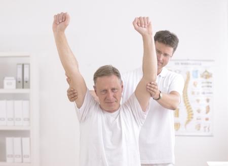aide � la personne: L'homme de physioth�rapie et physioth�rapeute senior au bureau