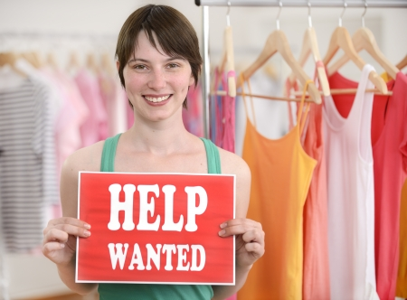 business owner: Happy proud owner of store with help wanted sign