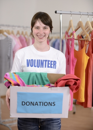 Volunteer with clothes donation box at second hand store Stock Photo