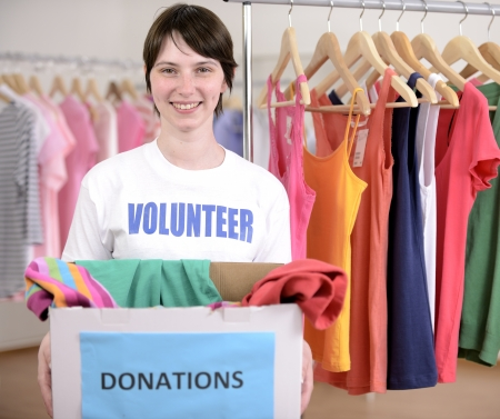 charitable: Volunteer with clothes donation box at second hand store Stock Photo