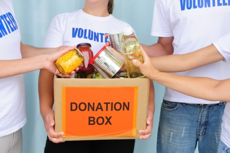 volunteering: volunteer putting food in a donation box