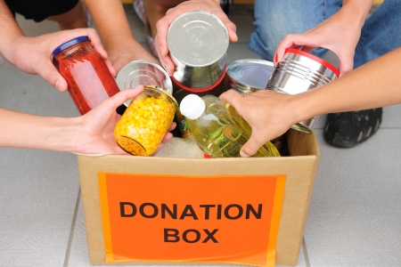 donations: volunteer putting food in a donation box