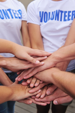 volunteering: volunteer group hands together showing unity
