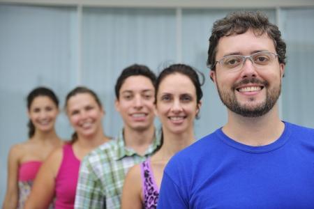 mid adult man: grupo feliz y diverso de personas reales ocasionales, hombre de mediana edad en frente