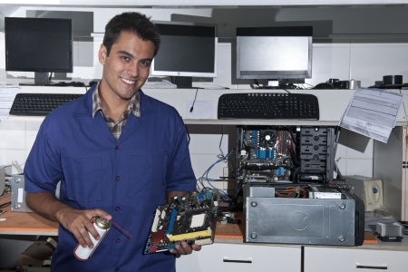 Small business: computer technician with motherboard at workshop photo