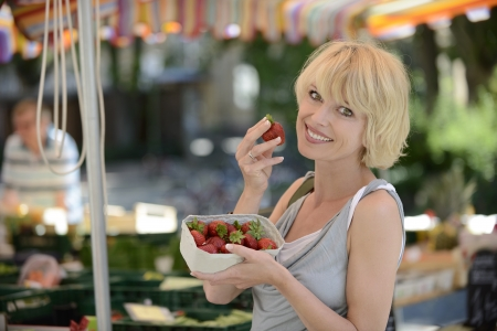 Happy woman buying strawberries at farmers market photo
