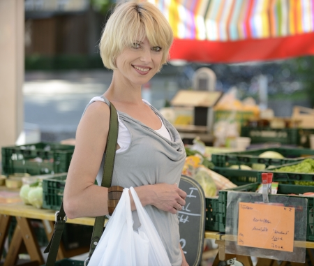 peasant: Happy woman buying vegetables at farmers market Stock Photo