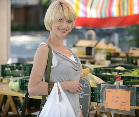 campesino: Mujer feliz de comprar verduras en el mercado agr�cola