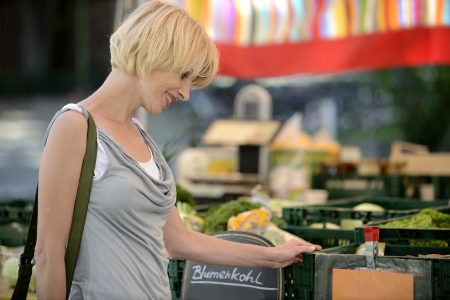 Happy woman buying vegetables at farmers market photo