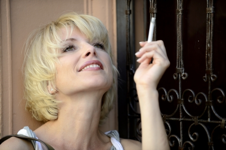 happy woman smoking a cigarette smiling photo