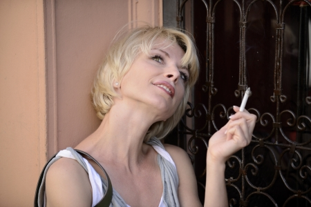 happy woman smoking a cigarette smiling Stock Photo - 14712620