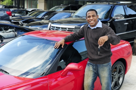 car dealer: happy man showing key of new red sports car Stock Photo