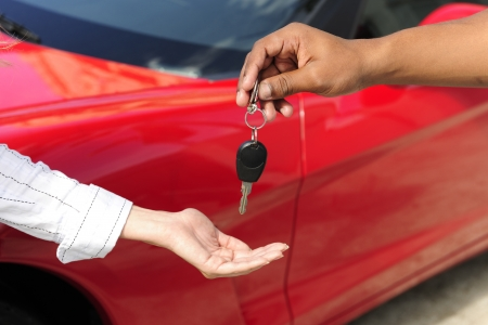 auto leasing: car dealership: woman receiving car key from salesman
