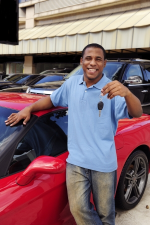 happy man showing key of new red sports car Stock Photo