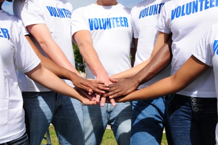 volunteering: multi-ethnic volunteer group hands together showing unity
