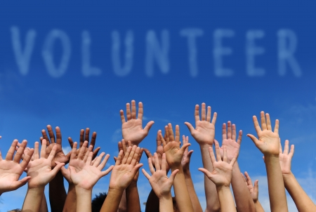 volunteering: volunteer group raising hands against blue sky background