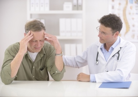 Doctor comforting mature male patient photo