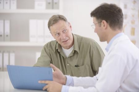 medico con paciente: Doctor hablando con el paciente var�n maduro Foto de archivo