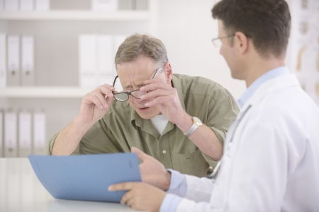 myopic: Doctor showing results to myopic or bewildered patient at office