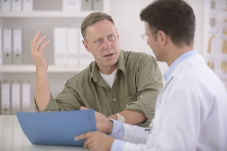 agitated: Doctor talking to mature male patient Stock Photo