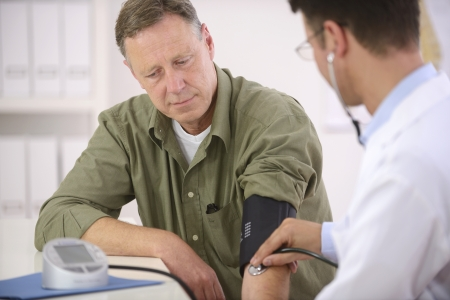 Doctor checking blood pressure of his patient photo