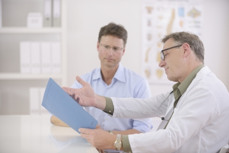 exam results: Healthcare: Doctor and patient discussing blood-test results Stock Photo