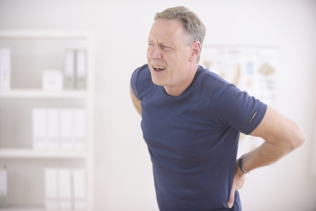 herniated: Man suffering from backache at office Stock Photo