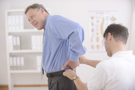 Chiropractic: Chiropractor examining senior man at office photo