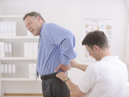 Physiotherapy: Physiotherapist examining senior man at office photo
