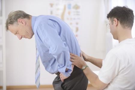 fisioterapia: Fisioterapia: Fisioterapeuta examen de hombre mayor en la oficina