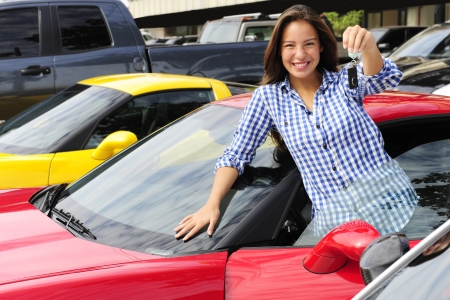 car dealers: happy woman showing key of new sports car