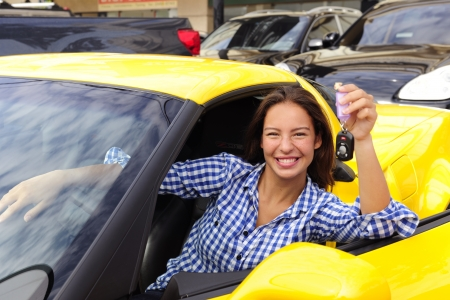 car dealers: happy woman showing keys  of her new yellow sports car