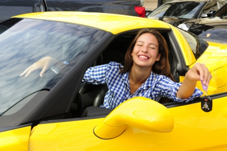 millonario: mujer feliz mostrando las claves de su nuevo coche deportivo yewllo