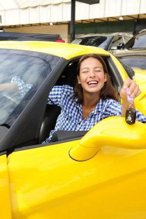 happy woman showing sitting inside of her new yellow sports car photo