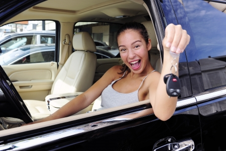 happy woman showing keys of her new expensive 4x4 off-road vehicle photo