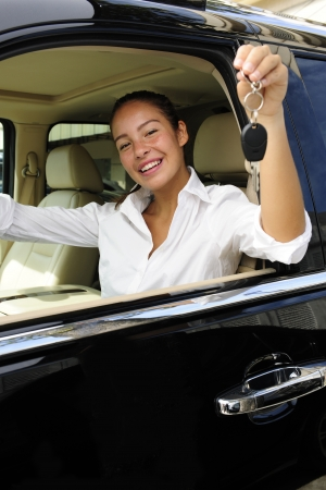 businesswoman showing keys of her new expensive  off-road vehicle photo