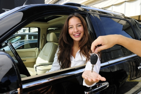car keys: businesswoman receiving keys of her new off-road car from dealer Stock Photo